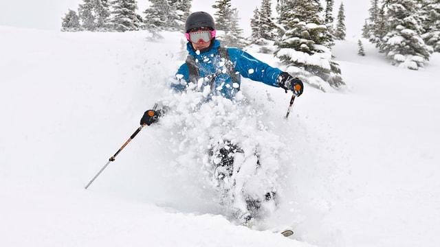 Skifahrerin fährt durch Tiefschnee.