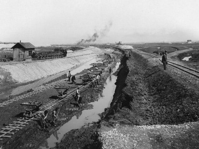 Schwarzweissbild von Arbeitern, die einen Kanal graben