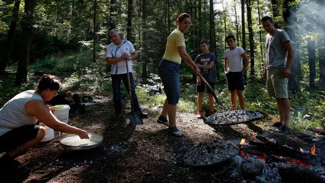 Eine Gruppe von Menschen macht Feuer im Wald.