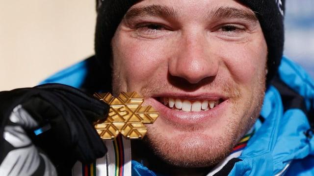 Mann zeigt stolz seine Goldmedaille