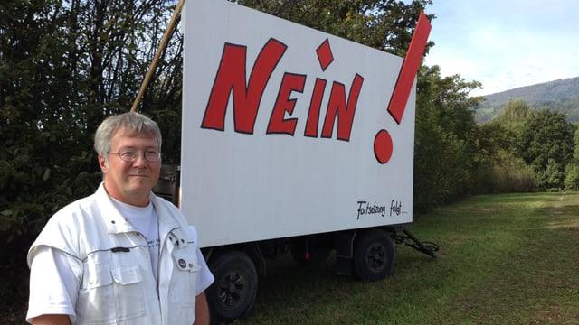 Raphael Steiner steht ausserdem von Meinisberg vor dem Plakat mit der Aufschrift «Nein - Fortsetzung folgt», welches den Widerstand gegen den Fahrenden-Durchgangsplatz symbolisiert.