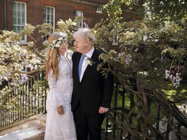 Carrie Johnson (im Hochzeitskleid) und Boris Johnson posieren für ein Foto