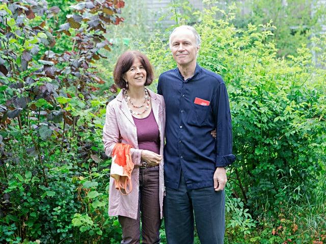 Das Ehepaar Fischer in ihrem Garten. Sie hält eine Badehose. Er hat den Schweizer Pass in der Hemdtasche.