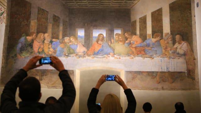 Touristen fotografieren das Wandgemälde vom letzten Abendmahl.