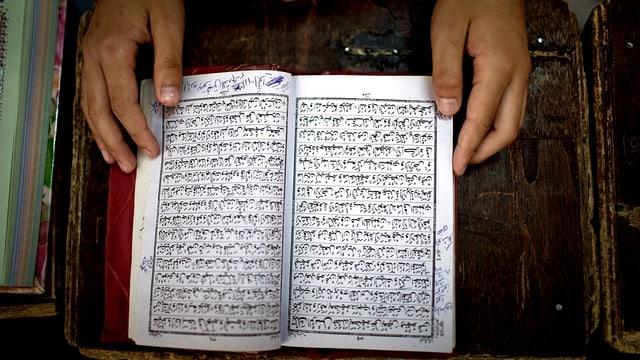Ein pakistanischer Schüler blättert im Koran.