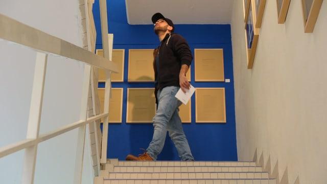 Ein junger Mann mit Jeans, dunklem Pullover und einem Cap auf dem Kopf in einem Treppenhaus.
