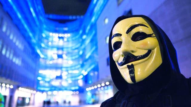 Ein Person in einem schwarzen Umhang und mit einer weissen Maske (Mund, Nase und Augen schwarz aufgemalt).