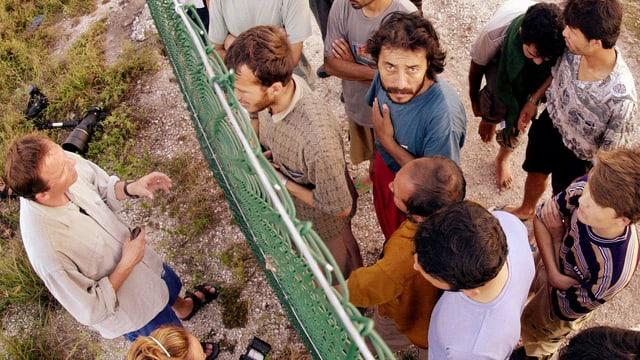 Flüchtlinge auf Nauru von oben fotografiert diskutieren mit einem Mann durch einen Zaun
