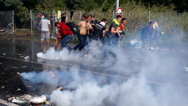 Fugitivs che scappan suenter che la polizia ha duvrà gas lacrimogen e chanuns d'aua cunter els.