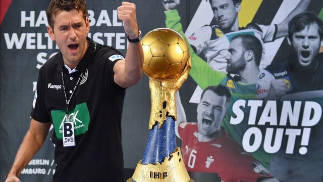 Deutschlands Coach Christian Prokop (l.) neben dem WM-Pokal.