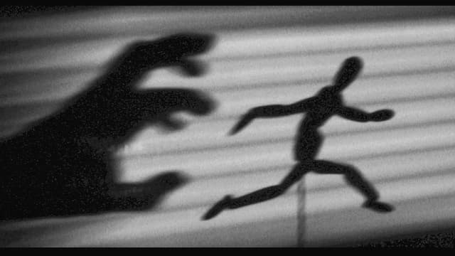 Schattenbild: Eine Hand greift nach einer rennenden Person.