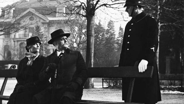 schwarzweiss Bild von einem Paar auf der Bank und einem Polizisten