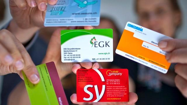 Frauen und Männer zeigen die Versicherungskarten ihrer verschiedenen Krankenversicherungen.
