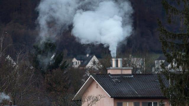 Heizungs-Rauch und Dampf über einem Dach.