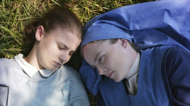 Ein Mädchen und eine mit blauem Nonnen-Kleid liegen nebeneinander in einer Wiese.