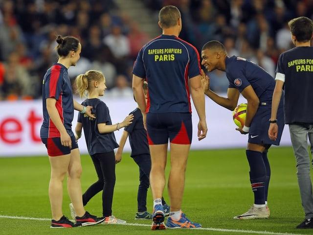 Mbappé begrüsst Pariser Feuerwehrleute und ihre Kinder vor dem Anpfiff.