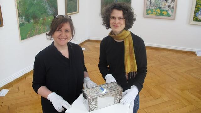 Direktorin und ihre Stellvertreterin arrangieren ein Kunstwerk