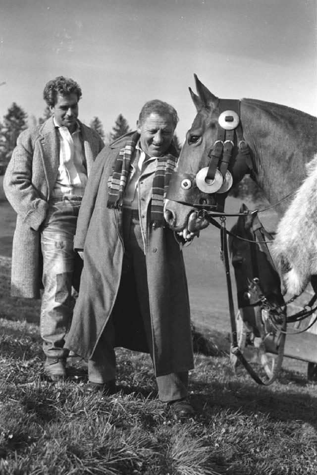 Zwei Männer auf einem Feld im Frühlingsmantel. Der ältere der zwei streichelt ein Pferd.