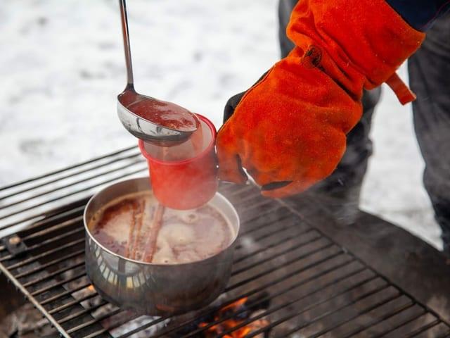 Mit einem Lederhandschuh wird aus einer Pfanne, die auf dem Feuer steht Orangenpunsch serviert.