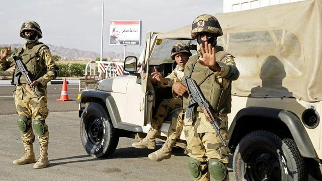 Bewaffnete und vermummte Soldaten in Tarnuniformen und schussicheren Westen vor einem Militärjeep, im Hintergrund ein Plakat mit dem Konterfei Al Sisis.