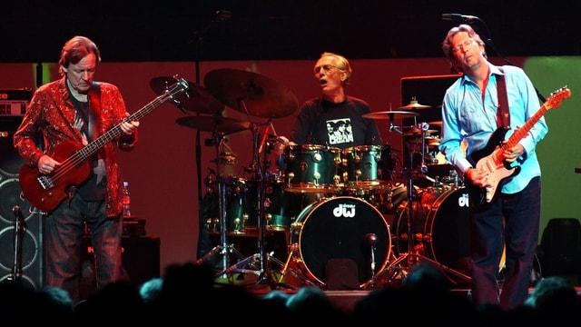 Bassist, Schlagzeuger und Gitarrist auf einer Bühne