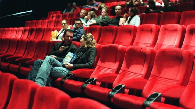 Einige Personen sitzen in einem Kinosaal in der Stadt Zürich.