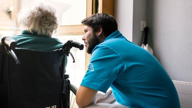 Junger Mann spricht mit alter Frau in einem Rollstuhl.