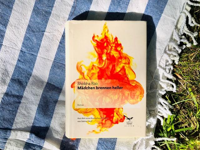 Der Roman «Mädchen brennen heller» von Shobha Rao liegt auf indischem Tuch.