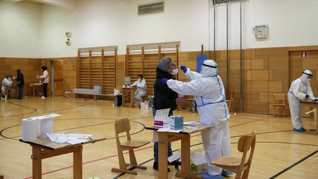 Menschen in Bozen machen Corona-Test in einer Turnhalle.