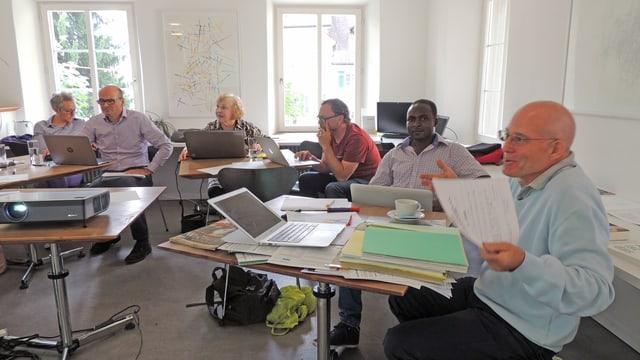Sechs Personen sitzen an Pulten. Vor sich Computer und Papierstapel.