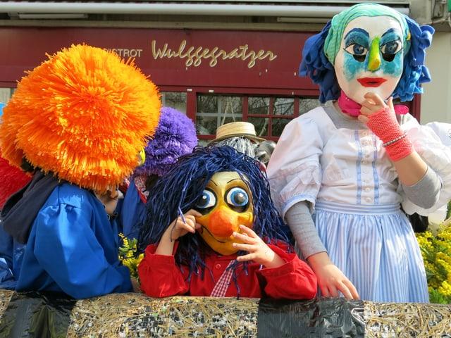 Drei kostümierte Kinder auf Strohwagen.