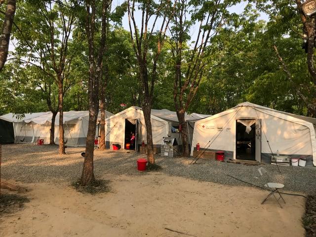 Zwischen Bäumen stehen drei grosse Zelte - eines für Männer, eines für Frauen, eines für Kinder.