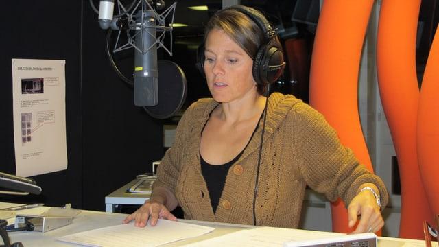 Die Moderatorin sitzt im Radiostudio vor einem Mikrofon.