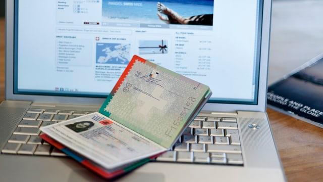 Ein Pass liegt auf einem Laptop, auf dem Bildschirm die Website einer Fluggesellschaft.
