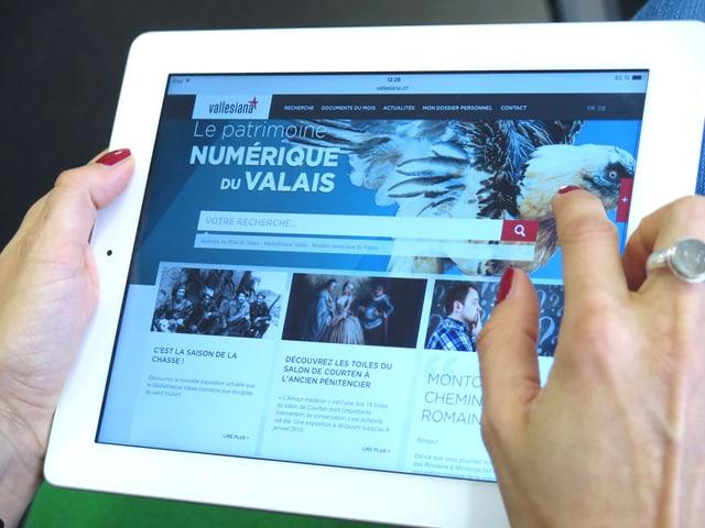Zwei Frauenhände halten ein iPad, darauf ist die Website Vallesiana zu sehen.
