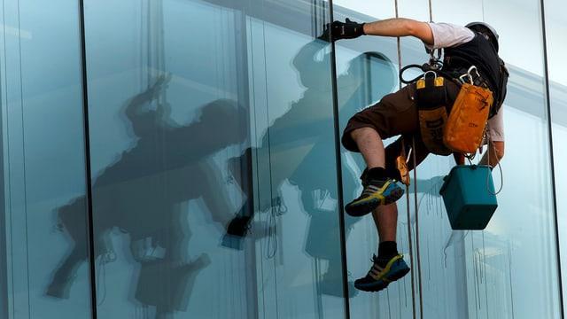 Ein Gebäudereiniger hängt angeseilt an einer Glasfasade.