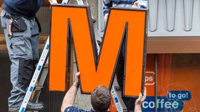 Arbeiter montieren ein Migros-Logo ab.