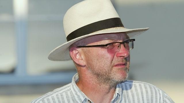 Ein Portrait von Regisseur Leopold Huber. Er trägt eine Brille und einen Hut.