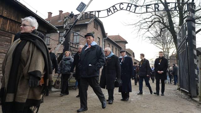 Menschen beim Eingangstor zum KZ Auschwitz.