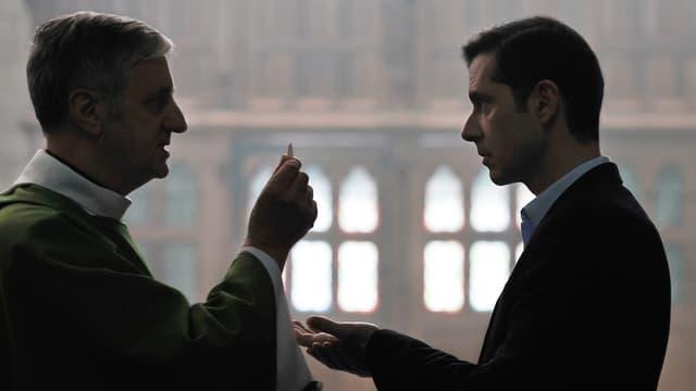 Ein Priester reicht einem Mann in einer Kirche eine Hostie.