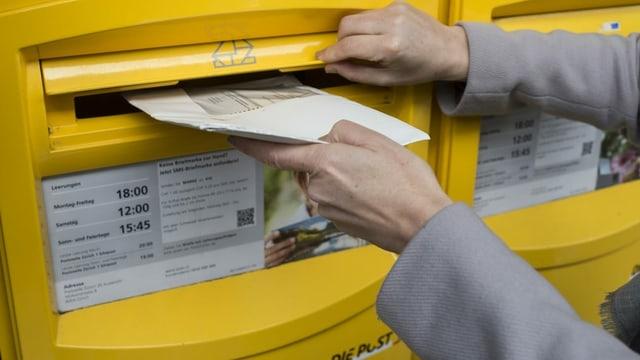 Eine Person wirft ein Stimmkuvert in einen Briefkasten.