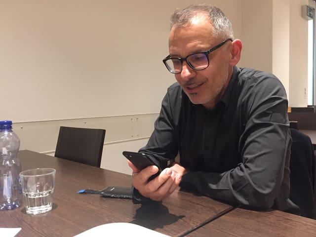 Mann mit Brille sitzt am Tisch und schaut auf sein Smartphone