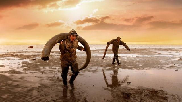 Zwei Männer mit Mammutstosszähnen auf den Schultern.