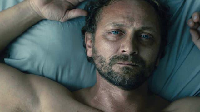 Ein Mann mit nacktem Oberkörper liegt auf einem Bett und starrt an die Decke