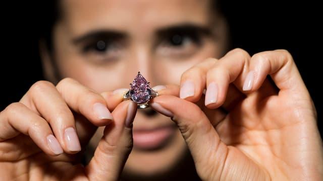 Eine Frau hält den Ring mit dem Edelstein in die Kamera.