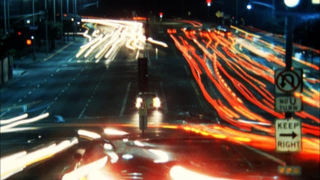 Langzeitbelichtung: Lichtspuren von Autos auf einer nächtlichen Strasse