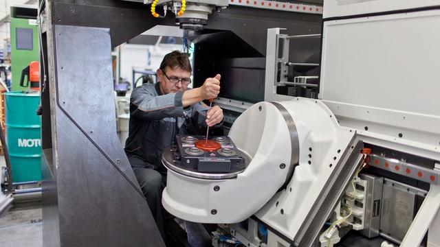 Ein Mann repariert eine Maschine.