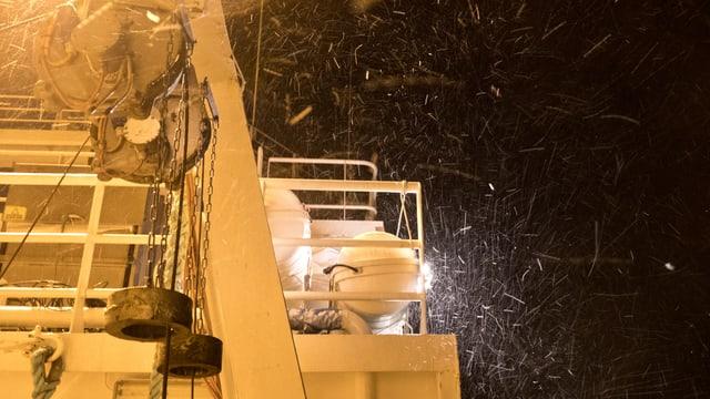 Ein Teil des Schiffs in gelbem Licht – man sieht Schnee.