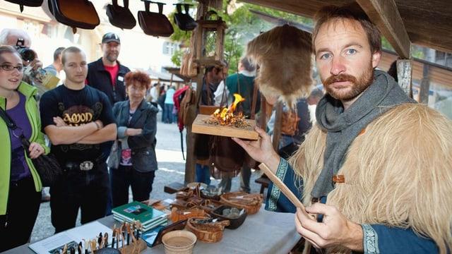 Mann zeigt kleines Feuer auf Holzbrettchen