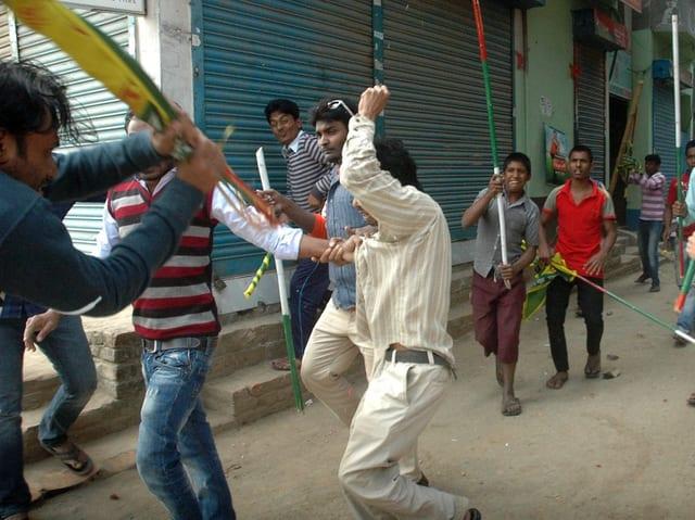 Mehrere Männer schlagen mit Stöcken auf einen Mann ein